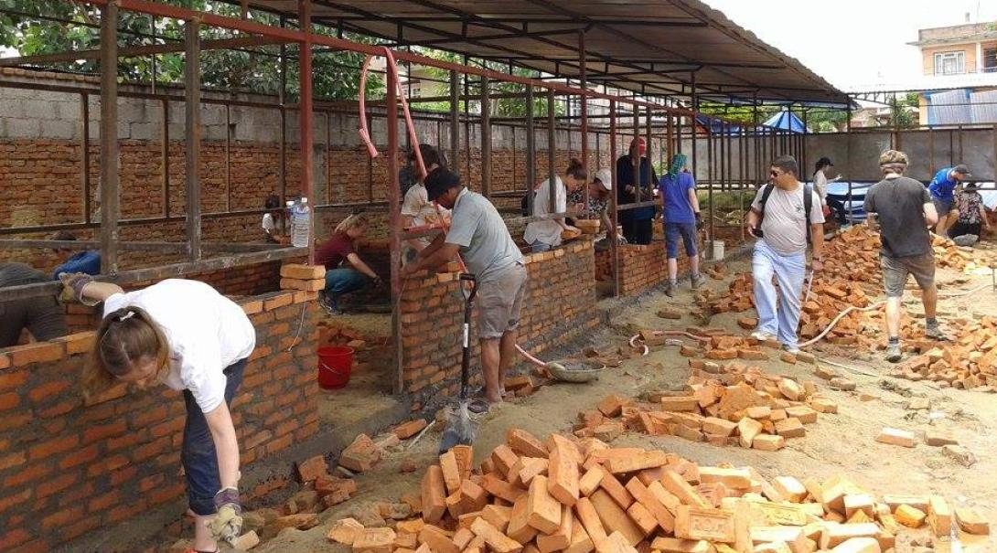 Building volunteers abroad constructing the walls of a primary school in Nepal during their building project